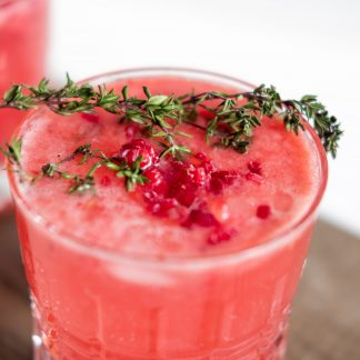 Sprig of thyme resting on top of a pink colored drink