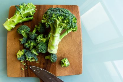 broccoli on brown wooden chopping board